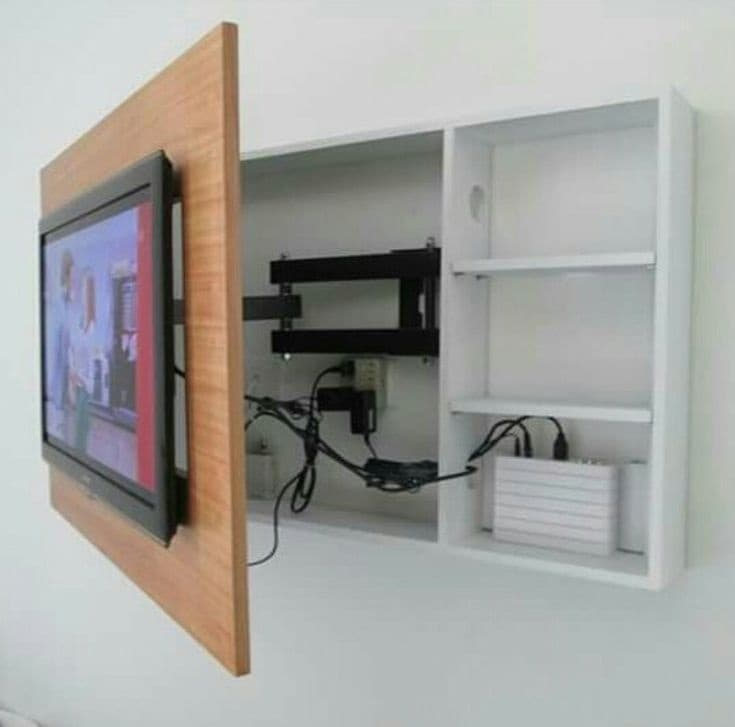 TV mounted on a wooden case  that is attached on a white wall. The wires are under the wooden case to keep them hidden.