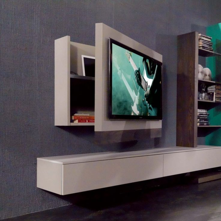 An LED TV mounted on a white wooden case that is attached to a grey wall.