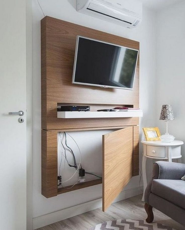 An LED Tv Mounted on a wooden case attached to a white wall with a drawer below it to keep wires hidden