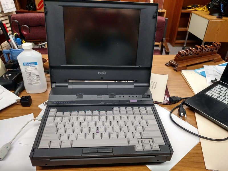 A Canon Note Jet 3 black Laptop with an open Lid Kept on a table