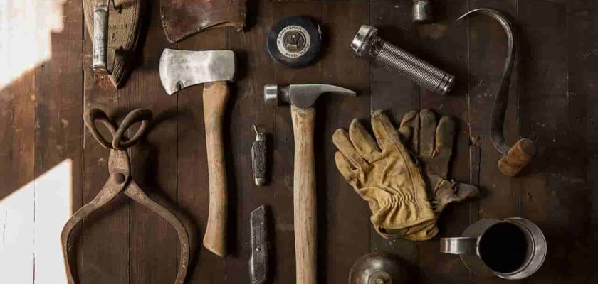 several old repairing tools like hammer and axe kept on a brown table