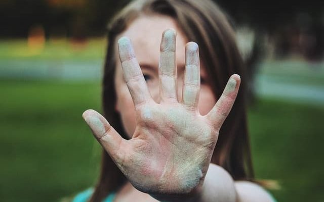 Girl showing her hands as a sign of stop
