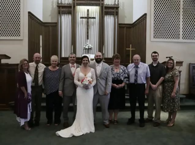 A group of people standing for a wedding photo shoot.  Captured by a Digital Camera.