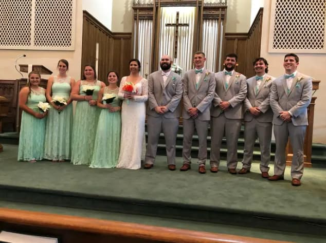 A group of people standing for a wedding photo shoot. Captured on an iPhone.